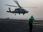 Navy Aviation Structural Mechanic Airman Cammron Jewell salutes an MH-60R Sea Hawk helicopter assigned to the Swamp Foxes of Helicopter Maritime Strike Squadron 74 as it lifts off from the flight deck of the aircraft carrier USS Dwight D. Eisenhower in the Arabian Gulf, Sept. 5, 2016. Navy photo by Petty Officer 3rd Class Nathan T. Beard