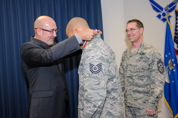 An ISR Airman receives a Larson Award medal from Lee Anthony, executive council representative, Freedom Through Viligance Association, Nov. 2 at 25th Air Force Headquarters, as Command Chief Master Sgt. Roger Towberman observes. (U.S. Air Force photo/William B. Belcher)