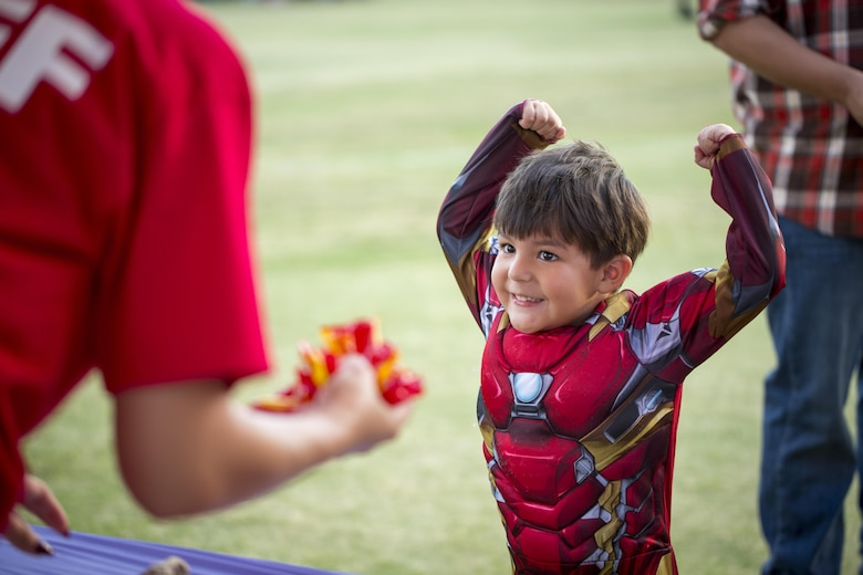 Aaron Espinoza, 3, son of Logan Espinoza, shows off his muscles while trick-or-treating at the Jack-O-Lantern Jubilee hosted by Marine Corps Community Services at Del Valle Field aboard the Marine Corps Air Ground Combat Center, Twentynine Palms, Calif., Oct. 28, 2016. (Official Marine Corps photo by Cpl. Levi Schultz/Released)