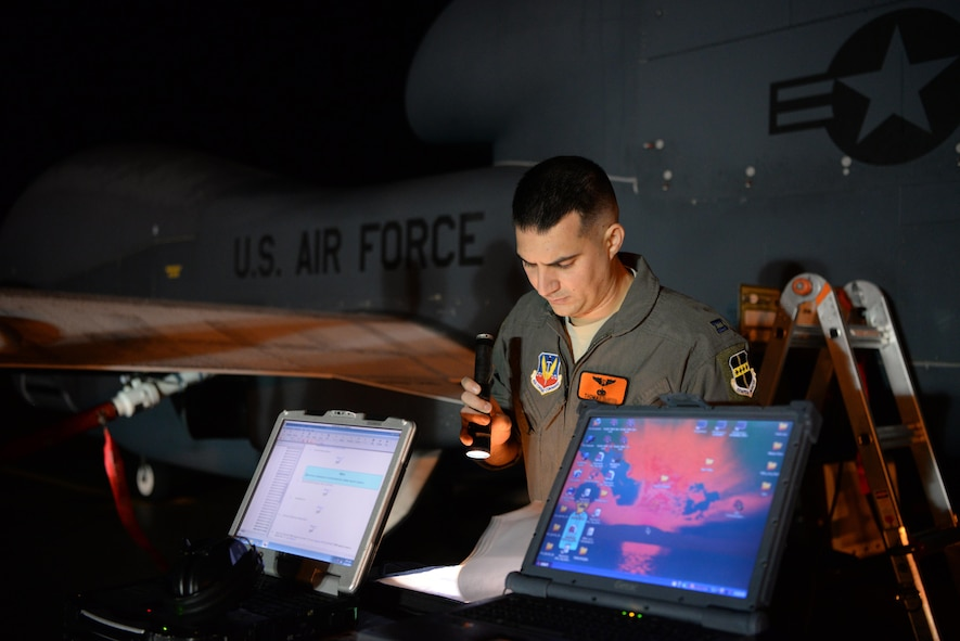"""Capt. Thomas, 12th Reconnaissance Squadron RQ-4 Global Hawk pilot, reviews a pre-flight checklist Nov. 1, 2016, at Beale Air Force Base, California. Thomas fulfilled the role of """"Hawkeye"""". Hawkeye is the call sign for the designated RQ-4 Pilot who performs pre-flight inspections for RQ-4 Global Hawks prior to flight. (U.S. Air Force photo/Staff Sgt. Bobby Cummings)"""
