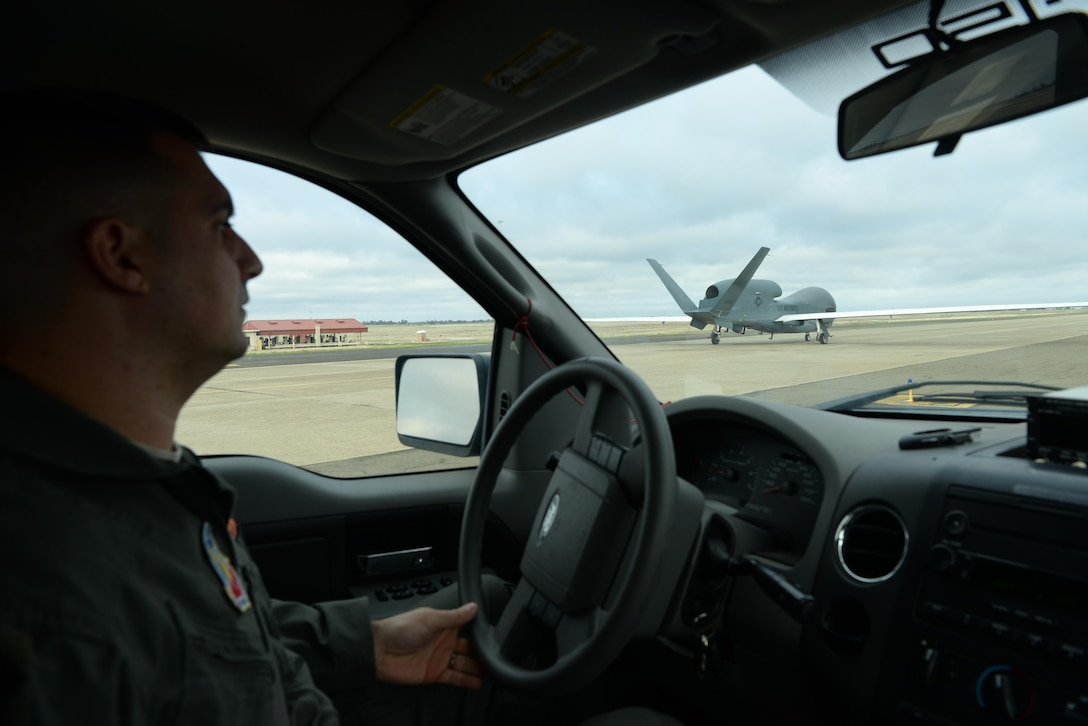 "Capt. Thomas, 12th Reconnaissance Squadron RQ-4 Global Hawk pilot, follows a RQ-4 Global Hawk down the taxiway Nov. 1, 2016, at Beale Air Force Base, California. Thomas fulfilled the role of ""Hawkeye"". Hawkeye serves as the human eyes and ears for the remotely piloted RQ-4 Global Hawk before flight. (U.S. Air Force photo/Staff Sgt. Bobby Cummings)"