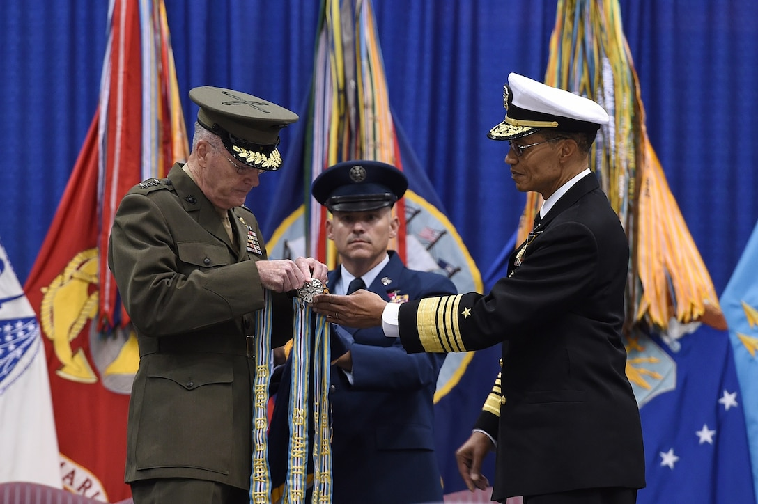 Chairman of the Joint Chiefs of Staff Gen. Joseph F. Dunford (left) attaches the Joint Meritorious Unit Award streamer on the U.S. Strategic Command (USSTRATCOM) guidon during a change of command ceremony at Offutt Air Force Base, Neb., Nov. 3, 2016. The award was presented to USSTRATCOM and its components, who distinguished themselves by exceptionally meritorious service from Nov. 16, 2013, to Nov. 3, 2016. Secretary of Defense Ash Carter presided over the change of command and thanked Adm. Cecil D. Haney (right), outgoing USSTRATCOM commander, for his service. He also congratulated Gen. John E. Hyten on his appointment as the new USSTRATCOM commander. Also pictured is USSTRATCOM Senior Enlisted Leader Chief Master Sgt. Patrick F. McMahon (center). Hyten previously served as commander of Air Force Space Command, and Haney will retire from active military duty during a separate ceremony in January. One of nine DoD unified combatant commands, USSTRATCOM has global strategic missions assigned through the Unified Command Plan that include strategic deterrence; space operations; cyberspace operations; joint electronic warfare; global strike; missile defense; intelligence, surveillance and reconnaissance; combating weapons of mass destruction; and analysis and targeting. (U.S. Air Force photo by Staff Sgt. Jonathan Lovelady)