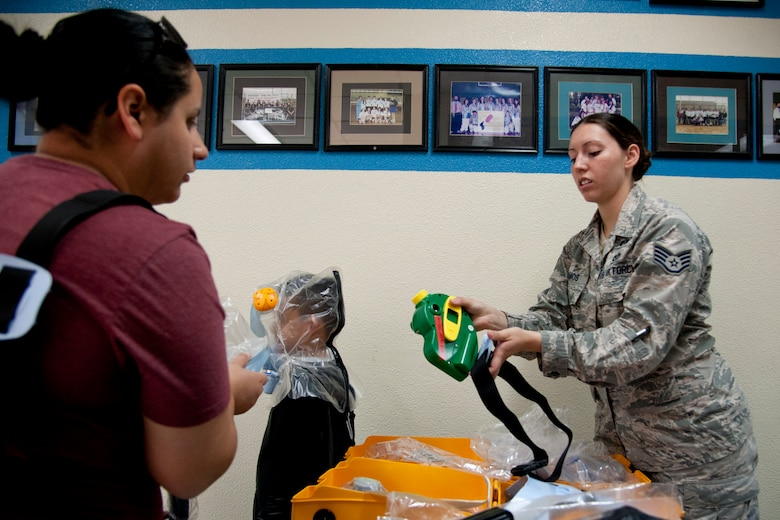 U.S. Air Force Staff Sgt. Kristina Ramos, 51st Civil Engineer Squadron NCO in charge of emergency management training, shows Stephanie Shufelt and her son Damian how to use an infant and child nuclear, biological and chemical positive-pressure protective system during exercise Courageous Channel 2016 at Osan Air Base, Republic of Korea, Oct. 29, 2016. During the exercise, families had a chance to wear and learn about the protective system that could protect them from nuclear, biological and chemical contaminates. (U.S. Air Force photo by Staff Sgt. Jonathan Steffen)