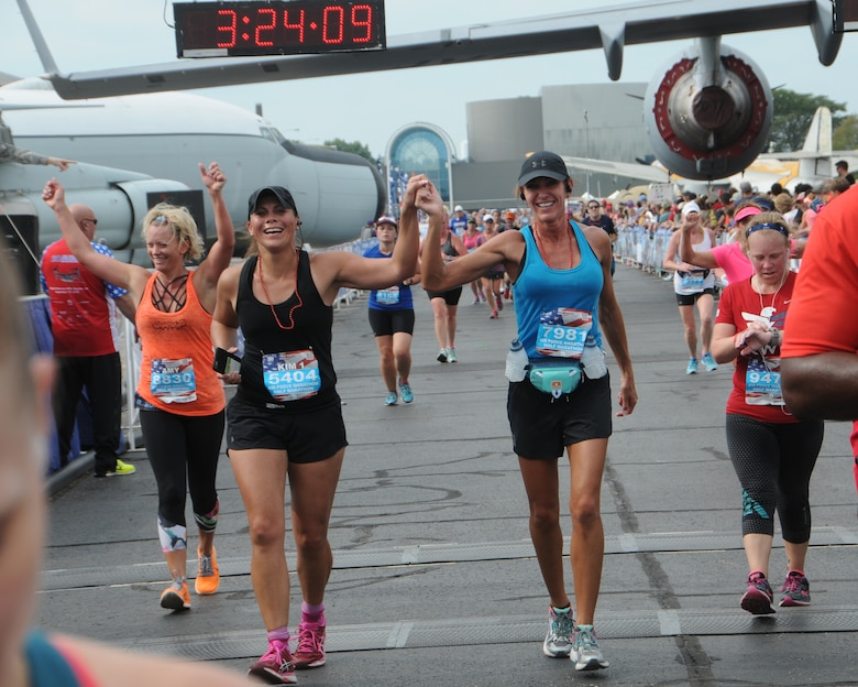 Senior Master Sgt. Kimberly Gunter, center left, and Master Sgt. Kimberly Robertson, center right, both members of the Montana Air National Guard,  hold hands as they cross the finish line at the 20th anniversary U. S. Air Force Marathon at Wright-Patterson Air Force Base, Ohio, Sept. 17, 2016. Gunter, was a first time half-marathon runner participant. (U.S. Air National Guard photo/Staff Sgt. Lindsey Soulsby)
