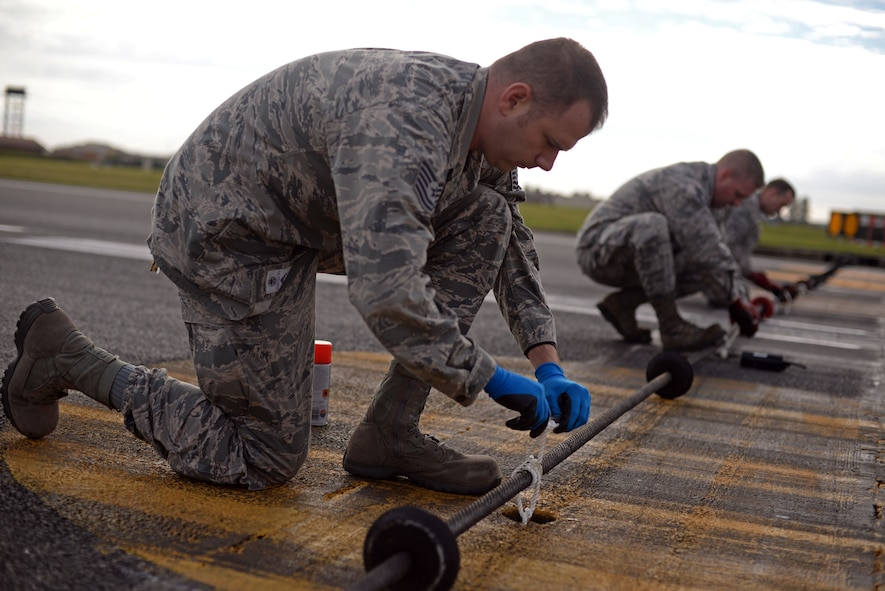 A U.S. Air Force Airmen from the 100th Civil Engineer Squadron power production shop tie down a Mobile Aircraft Arresting System cable Oct. 28, 2016, on RAF Mildenhall, England. The power production shop conducts a certification of the MAAS annually. (U.S. Air Force photo by Senior Airman Christine Halan)