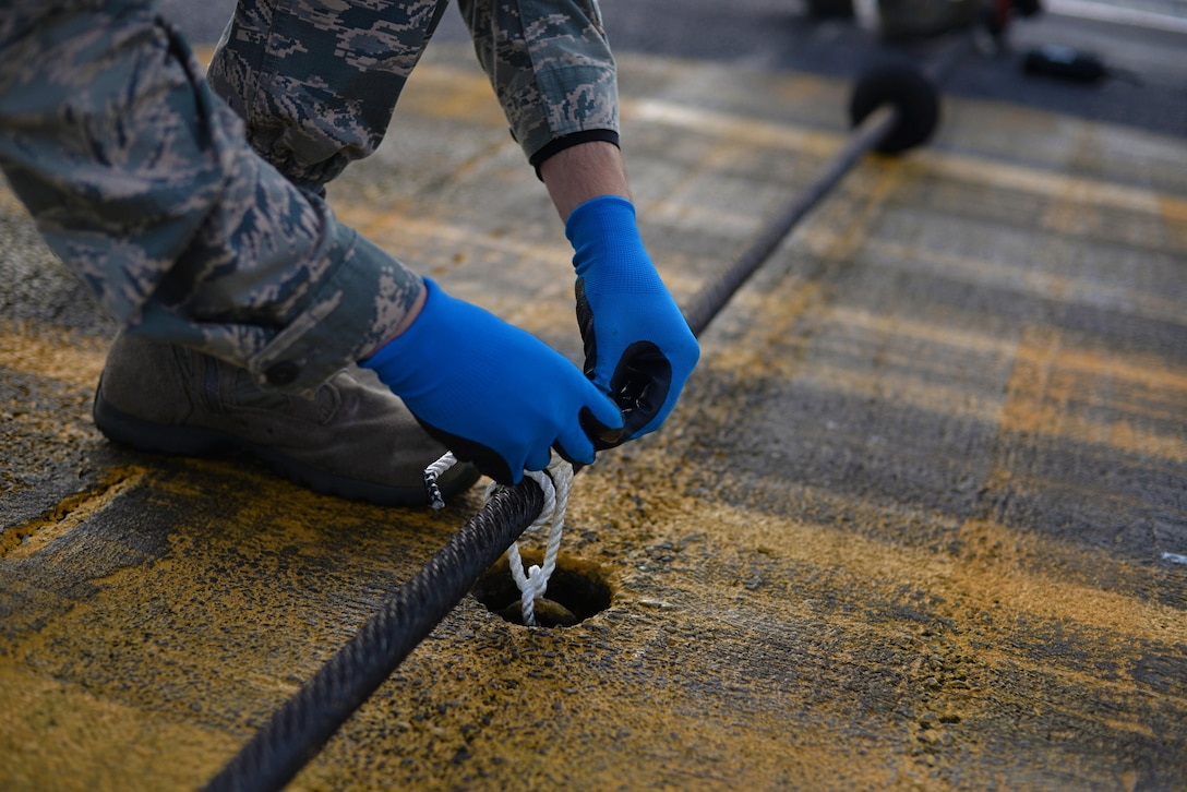 A U.S. Air Force Airman from the 100th Civil Engineer Squadron power production shop ties down a Mobile Aircraft Arresting System cable Oct. 28, 2016, on RAF Mildenhall, England. For optimum performance, the cable needs to be properly aligned and tied down to catch aircraft. (U.S Air Force photo by Senior Airman Christine Halan)