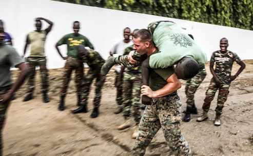 Staff Sgt. Michael Reinert, a training chief with Special Purpose Marine Air-Ground Task Force Crisis Response-Africa, demonstrates proper execution of the morning physical fitness session for sailors from the Benin Navy at Benin Naval Forces Headquarters, Cotonou, Benin, October 25, 2016. The U.S. Marine Corps theater security cooperation team with SPMAGTF-CR-AF spent two weeks teaching an NCO development and maintenance management course during their time training with the Benin Navy.  (U.S. Marine Corps photo by 1st Lt. Eric Abrams /released)