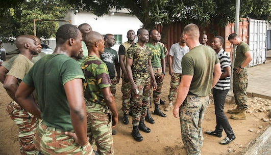 Staff Sgt. Michael Reinert, a training chief with Special Purpose Marine Air-Ground Task Force Crisis Response-Africa, talks to sailors from the Benin Navy following a physical fitness session at Benin Naval Forces Headquarters, Cotonou, Benin, October 25, 2016. The U.S. Marine Corps theater security cooperation team with Special Purpose Marine Air-Ground Task Force Crisis Response-Africa spent two weeks teaching an NCO development and maintenance management course during their time training with the Benin Navy.  (U.S. Marine Corps photo by 1st Lt. Eric Abrams /released)
