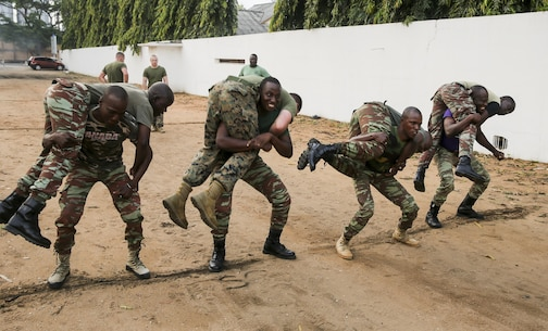 Sailors with the Benin Navy conduct buddy squats during a physical fitness session with U.S. Marines at Benin Naval Forces Headquarters, Cotonou, Benin, October 25, 2016. The U.S. Marine Corps theater security cooperation team with Special Purpose Marine Air-Ground Task Force Crisis Response-Africa spent two weeks teaching an NCO development and maintenance management course during their time training with the Benin Navy.  (U.S. Marine Corps photo by 1st Lt. Eric Abrams /released)