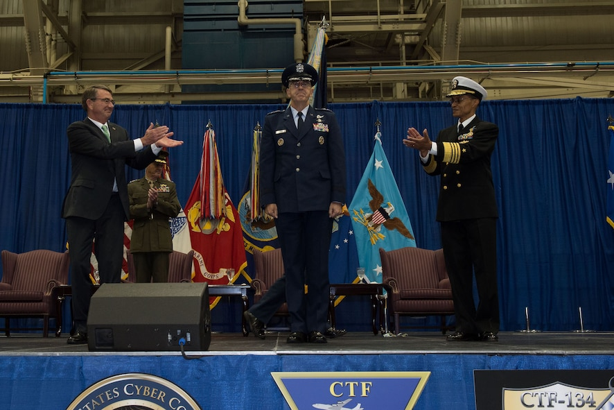 Defense Secretary Ash Carter applauds as Air Force Gen. John E. Hyten assumes the reins of U.S. Strategic Command from Navy Adm. Cecil D. Haney during a ceremony at Offutt Air Force Base.
