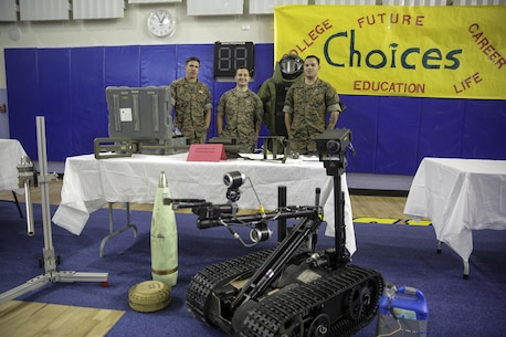 Explosive ordnance disposal technicians with Special Purpose Marine Air-Ground Task Force Crisis Response-Africa, stand behind their display table during a career day at Naval Air Station Sigonella, Italy, Oct. 25, 2016.  EOD Marines with SPAMGTF-CR-AF went to a Department of Defense high school to display capabilities and talk to students about their job during the event.  (U. S. Marine Corps photo by Cpl. Alexander Mitchell/released)