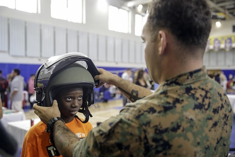 Staff Sgt. Bryce Morgan, an explosive ordnance disposal technician with Special Purpose Marine Air-Ground Task Force Crisis Response-Africa, puts the EOD 9 bomb suit helmet on a student during a career day at Naval Air Station Sigonella, Italy, Oct. 25, 2016.  EOD Marines with SPAMGTF-CR-AF went to a Department of Defense high school to display capabilities and talk to students about their job during the event.  (U. S. Marine Corps photo by Cpl. Alexander Mitchell/released)