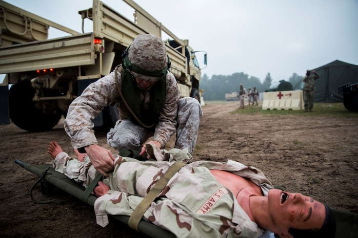 Sgt. Mathew W. Dearborn, data networking specialist with 4th Medical Battalion, 4th Marine Logistics Group, Marine Forces Reserve, searches a simulated casualty during Exercise Global Medic at Fort McCoy, Wisconsin, Aug. 17, 2016. Theater Medical Information Program-Marine Corps, the Corps' version of the joint medical software that supports medical providers in tactical environments, was put to the test during the medical exercise. The service-wide medical software suite gives medical units the tools they need to better locate, diagnosis and provide individualized care through each step of the medical process. (U.S. Marine Corps photo by Lance Cpl. Melissa Martens/Released)