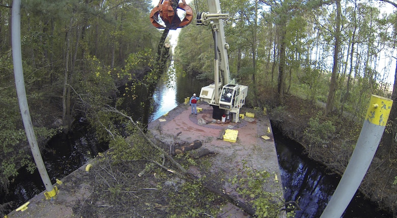 CHESAPEAKE, Va. -- Norfolk District Operations Branch personnel use a crane barge to remove downed trees along the Dismal Swamp Canal's Lake Drummond feeder ditch here October 27,2016. The trees came down during Hurricane Matthew, which inundated the area with water causing flooding, power outages and downed trees. (U.S. Army photo/Patrick Bloodgood)