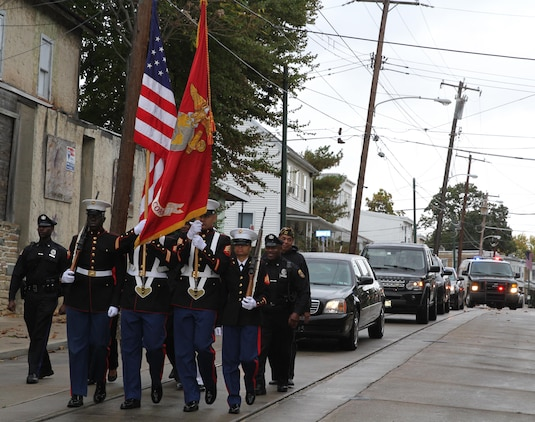 Marine reservists from Artillery Battery, 3rd Battalion, 14th Marine Regiment, carry the colors at the head of retired Lt. Gen. Ronald S. Coleman's vehicle convoy Oct. 22, 2016, in Darby, Pa. Coleman was being honored as a hometown hero during a street dedication ceremony. (U.S. Marine Corps photo by Cpl. Matthew Myers)