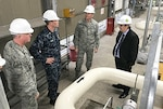Navy Lt. Cmdr. Joe Bossi, Fleet Logistics Center Yokosuka fuel director, shows DLA Energy Commander Air Force Brig. Gen. Martin Chapin (second from right) and other leaders a recently completed project that improves fuel pumping capability at Defense Fuel Support Point Hakozaki on the island of Azuma located within Tokyo Bay, Japan, Oct. 28.