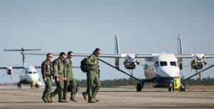 An aircrew walks by a C-145A Skytruck and C-146 Wolfhound on their way to their aircraft for a mission at Duke Field, Fla.  The 919th Special Operations Wing is the only wing in the Air Force that flies and maintains the Skytruck.  They are primarily used for new aircrew qualifications and flight proficiency missions.  (U.S. Air Force photo/Tech. Sgt. Sam King)