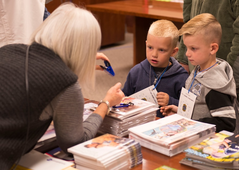 A representative from the Airman and Family Readiness Center gives two boys a paper clip at the Kids Understanding Deployment Operations day Oct. 21, 2016, at Mountain Home Air Force Base, Idaho. The children also received coloring books and other treats in their gift bags. (U.S. Air Force photo by Airman Jeremy D. Wolff/Released)