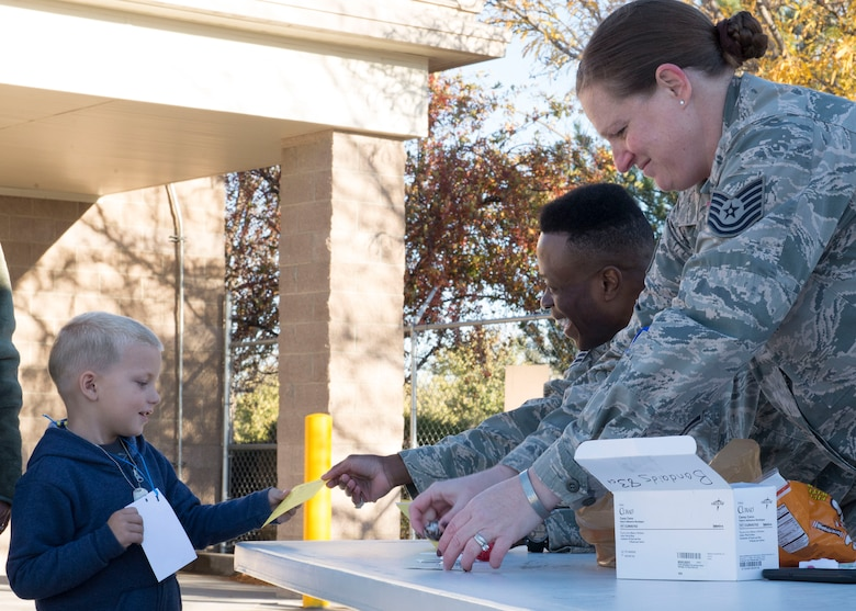 Children get their mock medical forms from the emergency medical technician stand at the Kids Understanding Deployment Operations day Oct. 21, 2016, at Mountain Home Air Force Base, Idaho. The event gave deployed service members' kids the opportunity to experience what their parents do before deploying. (U.S. Air Force photo by Airman Jeremy D. Wolff/Released)