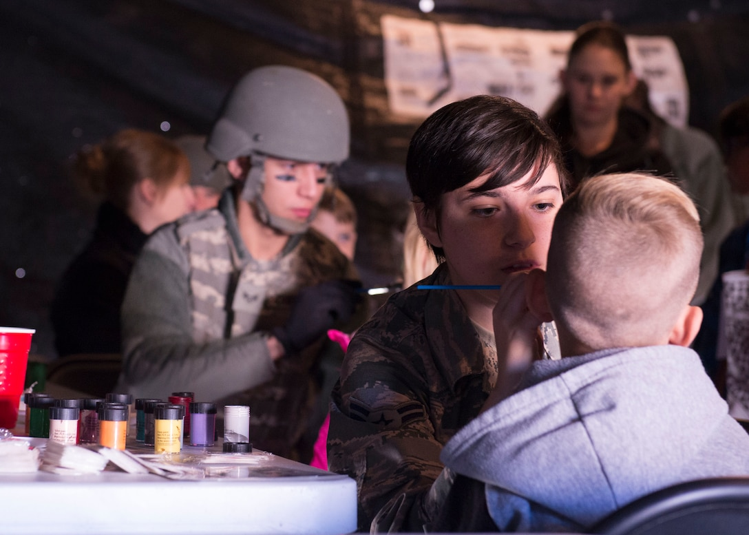 An airman paints a child's face at the Kids Understanding Deployment Operations day Oct. 21, 1016, at Mountain Home Air Force Base, Idaho. During the day, kids got a chance to have their faces painted and taste Meals Ready to Eat. (U.S. Air Force photo by Airman Jeremy D. Wolff/Released)