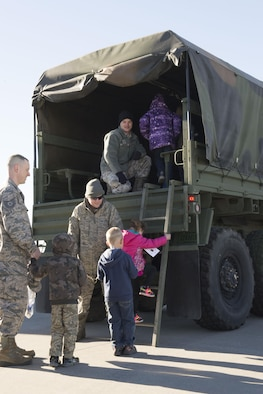 Airmen help a group of children onto a five-ton truck at the Kids Understanding Deployment Operations day Oct. 21, 2016, at Mountain Home Air Force Base, Idaho. The kids were given their own set of KUDOS dog tags, similar to the ones their parents wear. (U.S. Air Force photo by Airman Jeremy D. Wolff/Released)