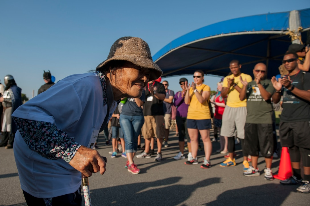 Eiko, a Kadena Special Olympics athlete, receives greetings and cheers from event volunteers during the athlete arrival event Nov. 5, 2016, at Kadena Air Base, Japan.  Approximately 1,000 American volunteers paired up with more than 500 local interpreters to support KSO athletes who ranged from six to 95 years of age. (U.S. Air Force photo by Senior Airman Peter Reft/Released)
