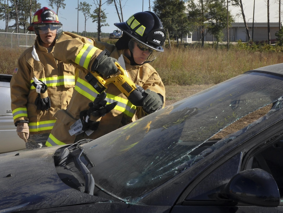 A 919th Special Operations Wing firefighter uses a saw to cut through a windshield during a car extraction training exercise at Duke Field, Fla., Nov. 6. The wing's firefighters took part in the exercise to meet their bi-annual training requirement.  (U.S. Air Force photo/Dan Neely)
