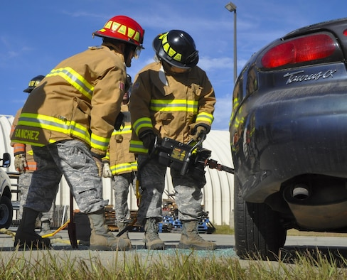 A 919th Special Operations Wing firefighter uses a prying tool to open the car door during an extraction training exercise at Duke Field, Fla., Nov. 6. The wing's firefighters took part in the exercise to meet their bi-annual training requirement.  (U.S. Air Force photo/Dan Neely)
