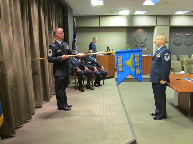 Chief David Miller, 710th Network Operations Squadron superintendent, holds the newly unfurled guidon, as Senior Master Sgt. James Abel, 710th Network Operations Squadron First Sergeant, looks on. The unit was activated during a ceremony at Robins Air Force Base, Ga., Nov. 6. (U.S. Air Force photo by 2nd. Lt. Michael Wisniewski)