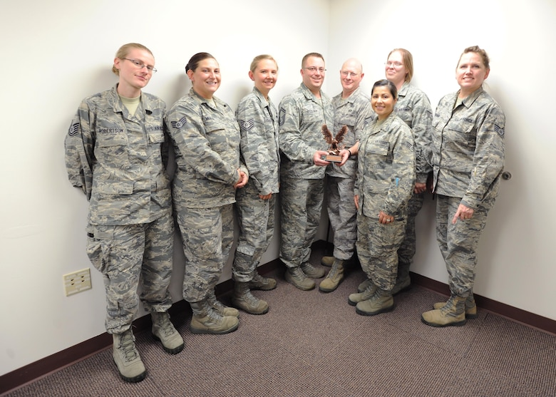 The 446th Force Support Squadron's Education and Training Flight holds up their 2015 Nathan Altschuler Outstanding Education and Training Program of the Year trophy November 6, 2016,  at Joint Base Lewis-McChord, Wash. In addition to winning the award for best education and training office in the entire reserve command, Senior Master Sgt. John Besselman, 446th FSS chief of force development, was named the Force Support Noncommissioned Officer of the Year for AFRC. (U.S. Air Force Reserve photo by Tech. Sgt. Bryan Hull)