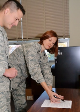 Capt. Hilary Styer, the full-time 111th Attack Wing judge advocate, reviews legal paperwork for Tech. Sgt. Thomas Stern, a 111th Security Forces Squadron security specialist, Nov. 11, 2016, at Horsham Air Guard Station, Pa. National Guard legal offices offer advice on civil, personal and legal matters. (U.S. Air National Guard photo by Tech. Sgt. Andria Allmond)