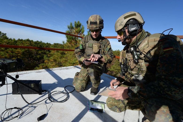 A picture of German armed forces Joint Terminal Attack Controllers, 1st Lts. Marius Sokol and Andreas Bier confirming laser designator codes.
