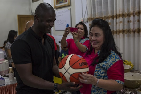 U.S. Marine Corps Sgt. Maj. Delwin K. Ellington, sergeant major of Marine All-Weather Fighter Attack Squadron (VMFA (AW)) 225, presents a signed basketball to Deysie Lumowa, the head mistress at Sekolah Menengah Atas Negeri 1 High School in Manado, Indonesia, Nov. 4, 2016. As part of a community relations event, the visit offered service members the opportunity to engage in cultural exchanges and build relationships within the local community. At the end of the event, Marines and Sailors exchanged gifts with Lumowa, showing each other's appreciation. (U.S. Marine Corps photo by Cpl. Aaron Henson)