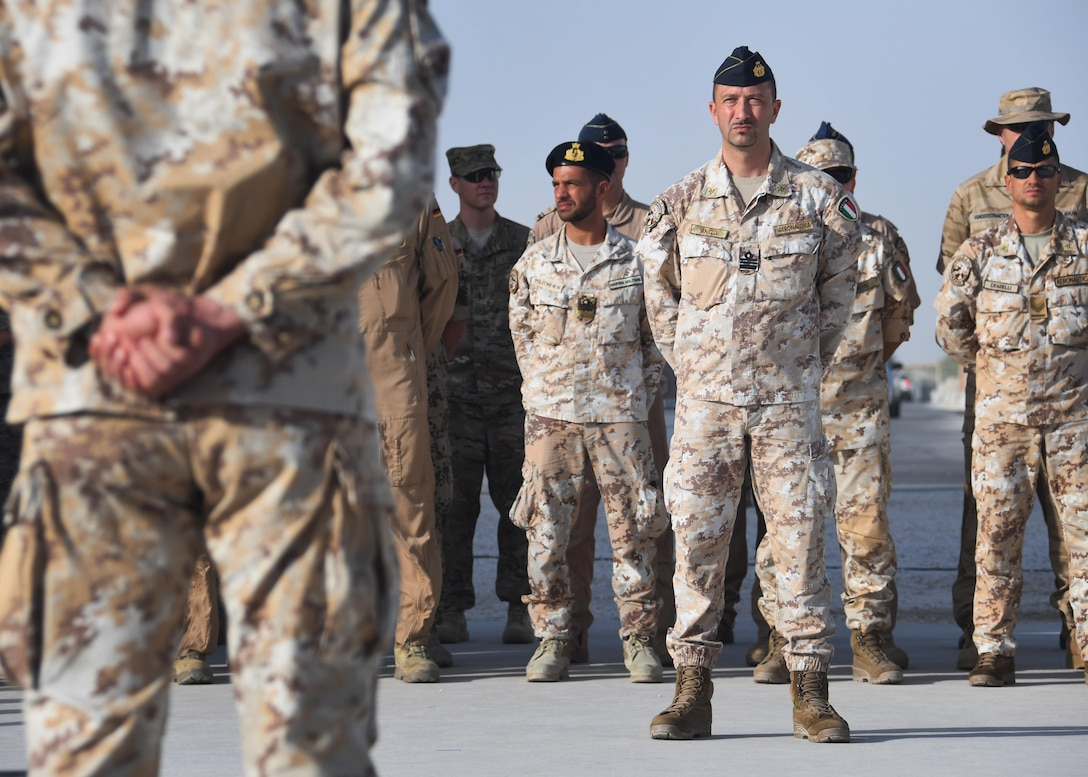 Members from the Italian Detachment at the Combined Air Operations Center stand in formation during the Italian Armed Forces Day ceremony at Al Udeid Air Base, Qatar Nov. 4, 2016. The ceremony was held in front of the Memorial Plaza and involved the raising of the Italian flag, a moment of silence and the presentation of certificates of appreciation. (U.S. Air Force photo by Senior Airman Miles Wilson)