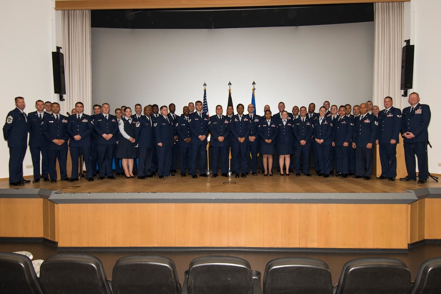 Col. Joe McFall, 52nd Fighter Wing commander, right, and Chief Master Sgt. Edwin Ludwigsen, 52nd FW command chief, left, pose with 52nd FW Airmen during a Community College of the Air Force graduation ceremony at the base theater at Spangdahlem Air Base, Germany, Nov. 4, 2016. The Airmen earned their associates degrees in various career-related fields as part of their completion from the largest community college in the United States. (U.S. Air Force photo by Staff Sgt. Joe W. McFadden/Released)