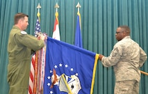 Chief Master Sgt. Michael Stephens, 552nd Air Control Wing's chief enlisted manager, holds the wing guidon as Colonel Bradley Bird, 552nd ACW vice commander, attaches the Meritorious Unit Award streamer.  (Air Force photo by Ron Mullan)
