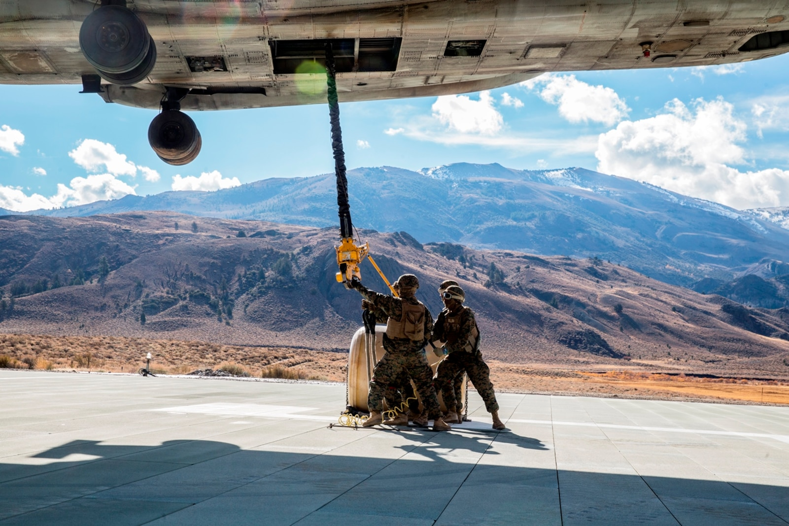 U.S. Marines with Combat Logistics Battalion 15, 1st Marine Logistics Group, and 3rd Battalion, 4th Marine Regiment, 1st Marine Division, grab a hook lowered by a CH-53E Super Stallion, with Marine Heavy Helicopter Squadron 466, to pick up a 500-gallon drum of water during a Helicopter Support Team drill at Mountain Warfare Training Center, Bridgeport, Calif., Oct. 25, 2016. The Marines use a pole to grab the hook lowered by the helicopter to ground the electrical currents before grabbing it by hand. The drum was taken into the Sierra Mesa Mountains to support Marines who are conducting field operations during Mountain Exercise 6-16. (U.S. Marine Corps photo by Lance Cpl. Adam Dublinske)