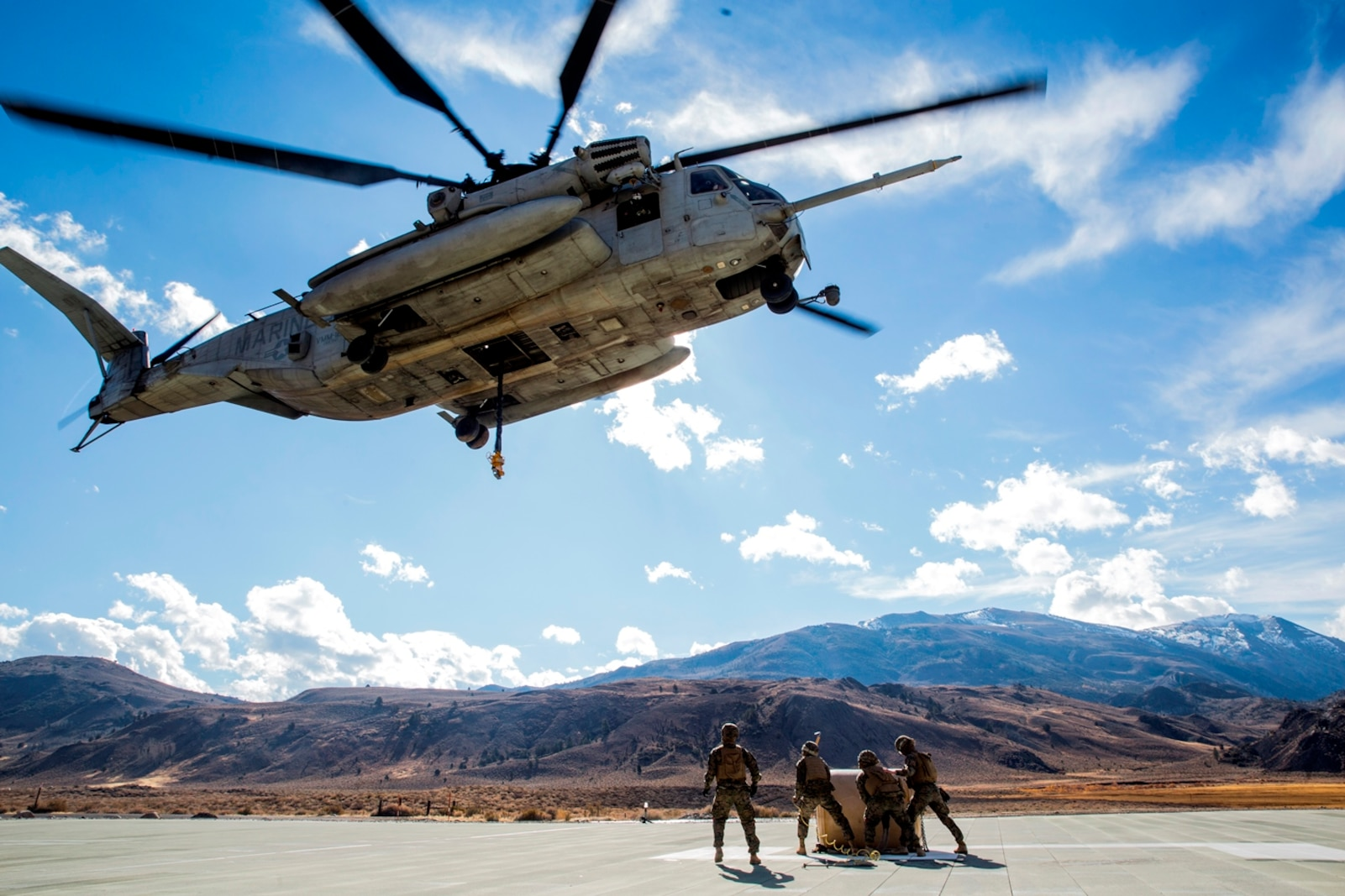A CH-53E Super Stallion, with Marine Heavy Helicopter Squadron 466, hovers to pick up a 500-gallon drum of water from U.S. Marines with Combat Logistics Battalion 15, 1st Marine Logistics Group and 3rd Battalion, 4th Marine Regiment, 1st Marine Division during a Helicopter Support Team drill at Mountain Warfare Training Center, Bridgeport, Calif., Oct. 25, 2016. The drum was taken into the Sierra Mesa Mountains to support Marines who are conducting field operations during Mountain Exercise 6-16. (U.S. Marine Corps photo by Lance Cpl. Adam Dublinske)