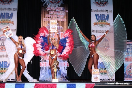 """Navy Lieutenant Kayla Tawoda (center), an air-naval gunfire liaison officer with I Marine Expeditionary Force command element, is awarded first place in the 2016 International Natural Bodybuilding Association Team USA Professional-Amateur competition. Bodybuilding is a disciplined and regimented process of physical conditioning that requires an extreme level of dedication. Tawoda said, """"My military core values translated really well into bodybuilding. There's so much discipline and willpower involved."""" (Courtesy Photo)"""