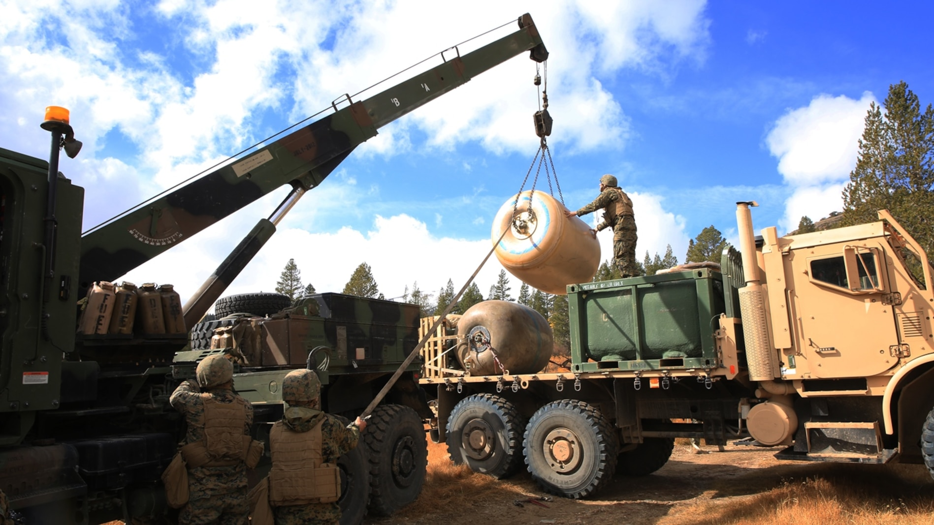 U.S. Marines with Combat Logistics Battalion 15, 1st Marine Logistics Group, load a 500-gallon drum of water on to the back of a Medium Tactical Vehicle Replacement at Mountain Warfare Training Center, Bridgeport, Calif., Oct. 23, 2016. The full drum weighs over 4,000 pounds and was airlifted into the area of operation to support Marine ground units by a CH-53E Super Stallion with Marine Heavy Helicopter Squadron 466. (U.S. Marine Corps photo by Lance Cpl. Austin Mealy)