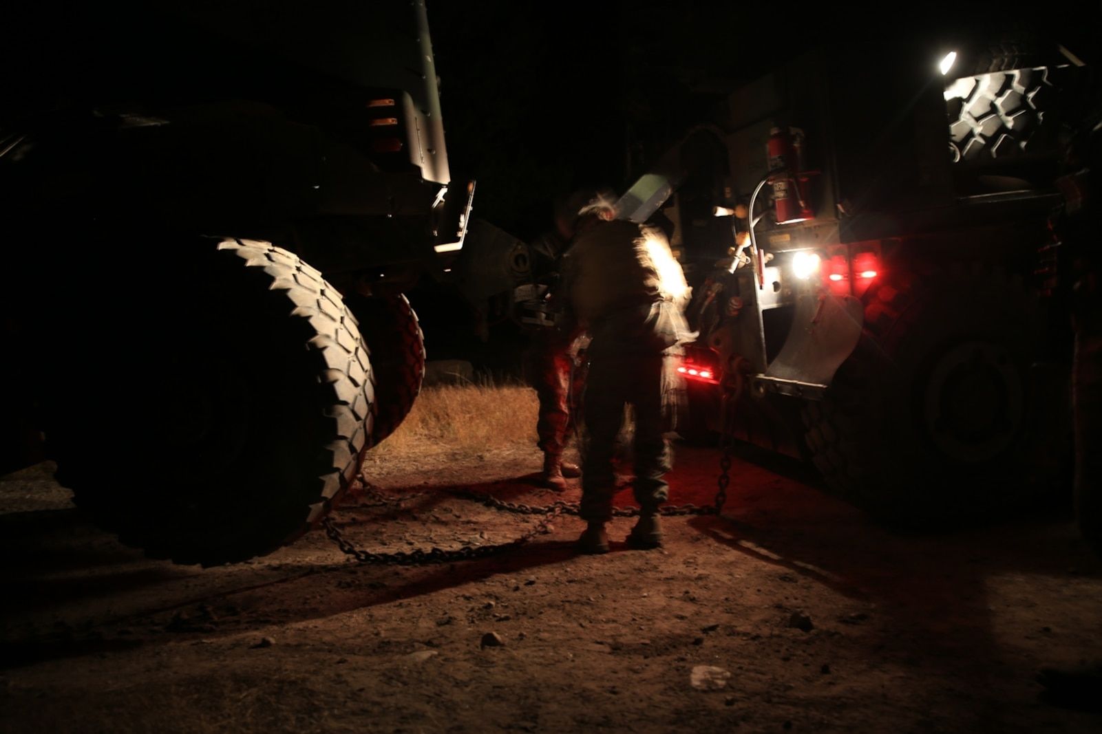 U.S. Marines Cpl. Jesse Gunderson and Lance Cpl. Juan Cerda attach tow cables from the AMK-36 wrecker vehicle to a broken Medium Tactical Vehicle Replacement at Mountain Warfare Training Center, Bridgeport, Calif., Oct. 23, 2016. The AMK-36 wrecker recovery vehicle's heavy tow capability made it possible for the Marines to get the immobile MTVR back down to the base of the mountain. Gunderson, a wrecker operator and Cerda, a motor transportation technician, are both with Combat Logistics Battalion 15, 1st Marine Logistics Group. (U.S. Marine Corps photo by Lance Cpl. Austin Mealy)