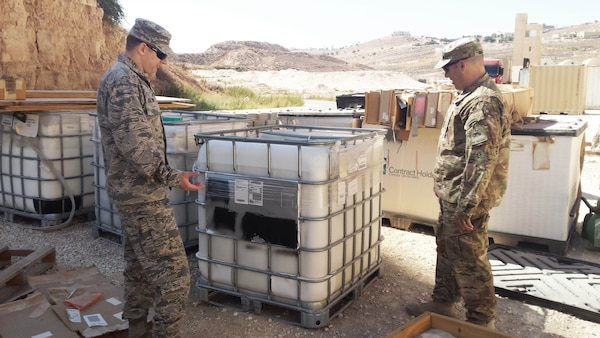 "An Army and an Air Force engineer review a pallet of containers of DLA-provided ground-hardening paste, commonly called ""rhino snot,"" which is used to reduce dust. This shipment was used to coat a makeshift runway for an unmanned aerial system."