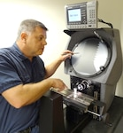 Test coordinator Jeff Grady demonstrates the dimensional test capability of an optical comparator.