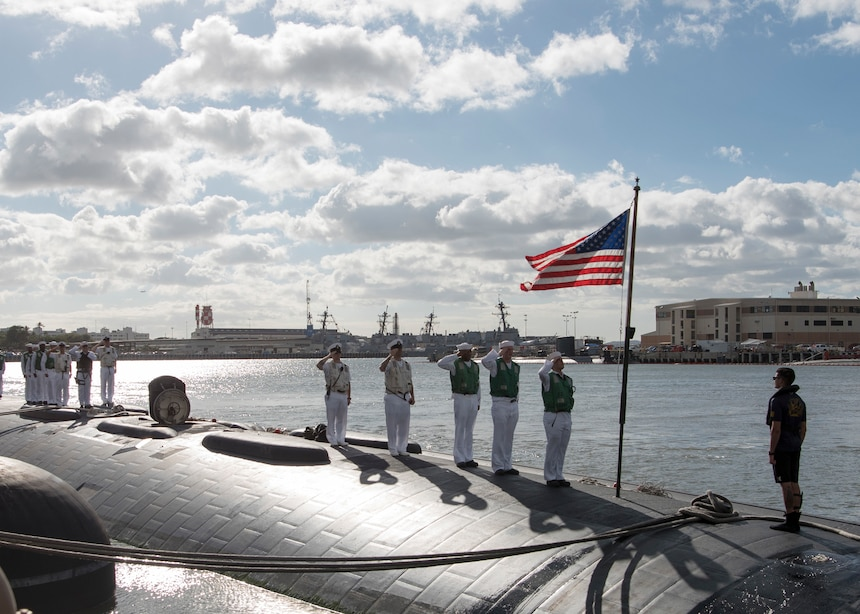 161103-N-LY160-124 JOINT BASE PEARL HARBOR-HICKAM, Hawaii (November 3, 2016) Sailors assigned to the Los Angeles-class fast-attack submarine USS Greeneville (SSN 772) salute the ensign following the completion of her six-month deployment to the Western Pacific Ocean in Joint Base Pearl Harbor-Hickam. (U.S. Navy photo by Petty Officer 2nd Class Michael H. Lee/Released)
