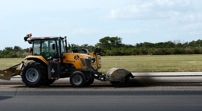 A tractor with a broom attachment sweeps asphalt debris into a pile along the runway at MacDill Air Force Base Fla., Oct. 27, 2016. Construction on MacDill's runway started Oct. 20, 2016 and is scheduled to be finished in 60 days. (U.S. Air Force photo by Senior Airman Tori Schultz)