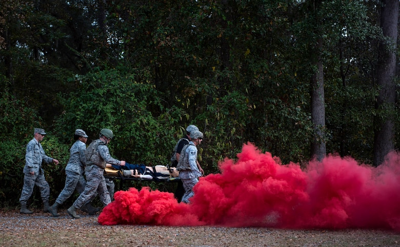 A team of medics transport a simulated casualty to a helicopter after an attack, during an Emergency Medical Technician refresher course, Nov. 4, 2016, at Moody Air Force Base, Ga. Medics navigated through smoke and debris, which altered their route to get the patients to safety. (U.S. Air Force photo by Airman 1st Class Janiqua P. Robinson)