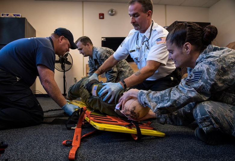 Students place a simulated casualty onto a gurney during an Emergency Medical Technician refresher course, Oct. 31, 2016, at Moody Air Force Base, Ga. During this skills assessment, evaluators made sure students correctly treated and evaluated injuries, used proper techniques to decrease the risk of further injury and used equipment properly to maintain the patient's safety. (U.S. Air Force photo by Airman 1st Class Janiqua P. Robinson)