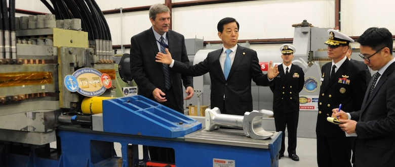 """In this file photo, """" Republic of Korea (ROK) Minister of National Defense Han Min-koo """" who led the ROK delegation to see new and emerging technologies developed at Naval Surface Warfare Center Dahlgren Division (NSWCDD) """" discusses electromagnetic railgun capabilities with his delegation and NSWCDD leadership, Oct. 19, 2016. Navy engineers briefed Han and his delegation on electromagnetic launchers, hypervelocity projectiles, and directed energy weapons, in addition to the command™s core capabilities in complex warfare systems development and integration to incorporate electric weapons technology into existing and future fighting forces and platforms."""