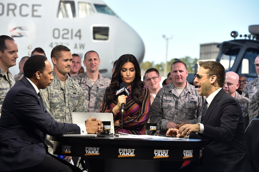 Max Kellerman, ESPN First Take co-host, Stephen A. Smith, ESPN First Take co-host, and Molly Qerim, ESPN First Take host, answers a question from an audience member here during First Take's week of Veteran's Day program, Nov. 7, 2016. Every year ESPN First Take honors service members near Veterans Day by telecasting their show from a different base and highlights service members who go above and beyond in their careers.