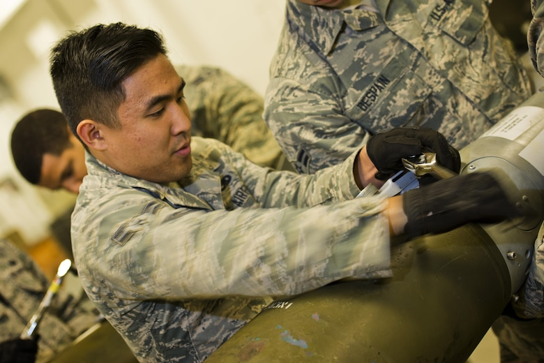 Airman 1st Class Joseph Lee, 5th Munitions Squadron line delivery crew chief, tightens screws on a GBU-38 tail assembly at Minot Air Force Base, N.D., Oct. 27, 2016. During bomb building, screws are tightened to secure the tail guidance kit on an inert 500 lb. MK82 bomb. (U.S. Air Force photo/Airman 1st Class J.T. Armstrong)